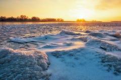 Winterlandschaft mit gefrorenem See und brennendem Himmel des Sonnenuntergangs stockfotografie