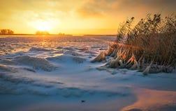 Winterlandschaft mit gefrorenem See und brennendem Himmel des Sonnenuntergangs stockfoto