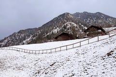 Winterlandschaft mit hölzernen Hütten und Berg in kleinem alpinem v Lizenzfreie Stockbilder