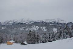Winterlandschaft mit Holzhäusern, Bäumen und Bergen auf Hintergrund nahe Garmisch-Partenkirchen deutschland Lizenzfreie Stockfotos