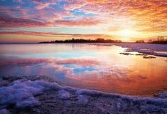 Winterlandschaft mit See und brennendem Himmel des Sonnenuntergangs. Lizenzfreies Stockfoto
