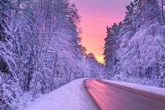 Winterlandschaft mit Sonnenuntergang, Straße und Wald Stockfoto