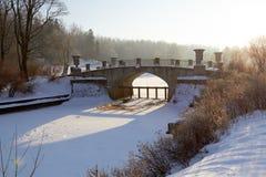 Winterlandschaft mit sonnigem Tag der alten Brücke Lizenzfreies Stockfoto
