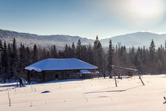 Winterlandschaft mit verlassenem Holzhaus Lizenzfreie Stockfotos