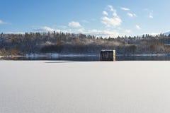 Winterlandschaft, See mit einer Verdammung im Vordergrund, gegen den Wald und den blauen bewölkten Himmel, schöne Natur, West-Ukr Stockfotografie