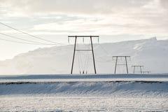 Winterlandschaft, Stromleitungen auf einem schneebedeckten Feld durch die Berge, Island Stockbilder