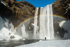 Winterlandschaft, Tourist durch berühmten Skogafoss-Wasserfall mit Regenbogen, Island Lizenzfreies Stockbild