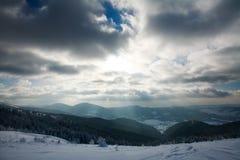Winterlandschaft von Bergen in den Strahlen der untergehenden Sonne stockfotografie
