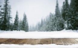 Winterlandschaft von Bergen und von hölzerner alter Tabelle mit Schnee Stockbild