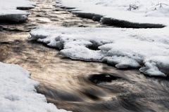 Winterliche Flussansicht mit Abendlicht, Wasserbewegung und Schnee lizenzfreie stockbilder