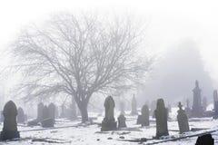 Winterlicher Kirchhof herein eingehüllt in Nebel Stockfotografie