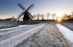 Winterlicher Sonnenaufgang über gefrorener Landschaft mit Windmühle stockbild