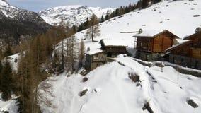 Winterluftbrummen establisher über schneebedecktem Stadt- und Waldholztal unter gefrorenen Bergen Schnee in der Gebirgsnatur stock footage