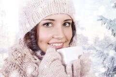 Wintermädchen, das warmes Getränk trinkt. Stockfoto