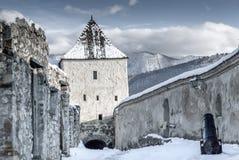 Wintermärchenschloss unter Schnee mit Bergen im Hintergrund stockfotografie