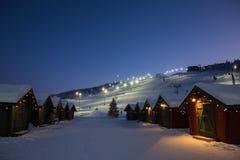 Wintermarktdorf in Levi, Finnland im evenig auf Skikabelweisenhintergrund Stockbilder