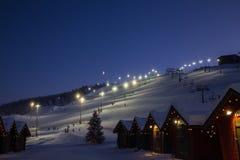 Wintermarktdorf in Levi, Finnland im evenig auf Skikabelweisenhintergrund stockfotografie