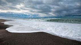 Wintermeereswellen, die Sandstrand am Morgen des stürmischen Wetters auf Ufer Schwarzen Meers von Abchasien schlagen Stockbild