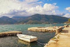 Wintermittelmeerlandschaft mit einem weißen Boot im kleinen Hafen montenegro Lizenzfreie Stockfotos