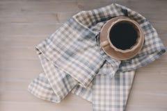 Wintermorgen zu Hause, Kaffee in der Schale mit Serviette auf grauem Holztisch Stockfotografie