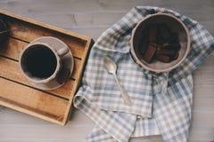 Wintermorgen zu Hause, Schokolade und Kaffee in der Schale mit Serviette auf grauem Holztisch Stockfotos