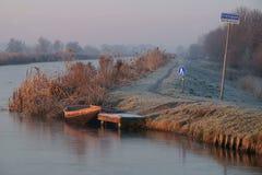 Wintermorning με το μαλακό κόκκινο φως του ήλιου και τον παγωμένο ποταμό Στοκ Φωτογραφία