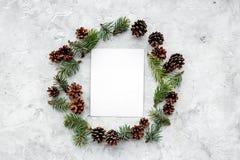 Wintermuster mit Fichtenzweig, Kegeln und leerem Blatt auf grauem copyspace Draufsicht des Hintergrundes Stockfoto