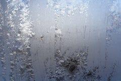 Wintermuster von Eiskristallen auf Glas Stockbild