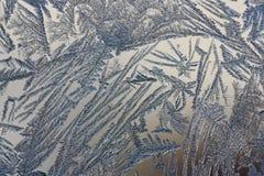 Wintermuster von Eiskristallen auf Glas Stockfoto