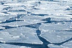 Blöcke des Eises auf gefrorenem blauem Meer Stockfotografie