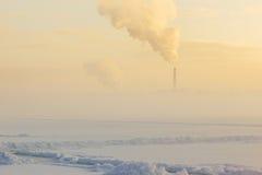 Winternebel über dem gefrorenen Fluss und die Fabrik leiten Lizenzfreie Stockfotografie