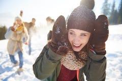 Winterpaare, die Spaß haben, draußen zu spielen im Schnee Stockbild