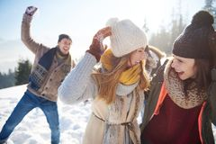 Winterpaare, die Spaß haben, draußen zu spielen im Schnee lizenzfreie stockfotografie