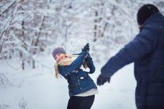 Winterpaare, die Spaß haben, draußen zu spielen im Schnee Junge frohe glückliche multi-racial Paare Stockfotos