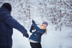Winterpaare, die Spaß haben, draußen zu spielen im Schnee Junge frohe glückliche multi-racial Paare Junge frohe Paare Lizenzfreie Stockbilder
