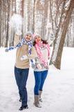 Winterpaare, die Spaß haben, draußen zu spielen im Schnee Winterpaare, die den Spaß spielt im Schnee im Freien haben Stockfoto