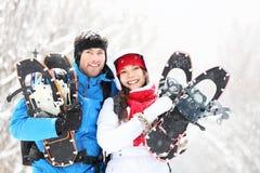 Winterpaare draußen auf Snowshoes Stockfotos