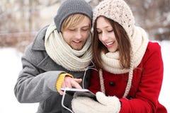 Winterpaare mit digitaler Tablette Stockfotos