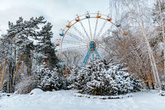 Winterpark und ferris Kreisanziehungskraft Schöne weiße Schneeszene mit Bäumen Stockfotografie