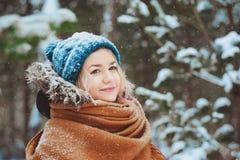 Winterporträt der glücklichen jungen Frau, die in schneebedeckten Wald in der warmen Ausstattung, in der Strickmütze und im Überf stockbild