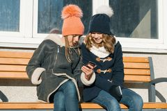 Winterporträt der Nahaufnahme im Freien von zwei Jugendlichestudenten im Profil lächelnd und sprechend, Mädchen, die Handy betrac lizenzfreie stockbilder