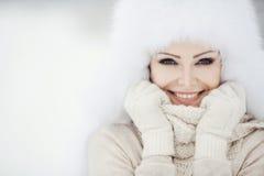 Winterporträt der schönen lächelnden Frau mit Schneeflocken in den weißen Pelzen Stockbild