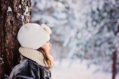 Winterporträt des entzückenden Kindermädchens im grauen Pelzmantel im schneebedeckten Wald Stockfotografie