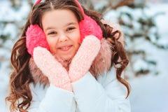 Winterporträt des glücklichen Kindermädchens im weißen Mantel und im Hut und des rosa Handschuhspielens im Freien lizenzfreies stockfoto