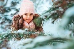 Winterporträt des glücklichen Kindermädchens im weißen Mantel und im Hut und des rosa Handschuhspielens im Freien stockbild