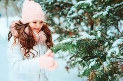 Winterporträt des glücklichen Kindermädchens im weißen Mantel und im Hut und des rosa Handschuhspielens im Freien stockbilder