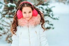 Winterporträt des glücklichen Kindermädchens im weißen Mantel und im Hut und des rosa Handschuhspielens im Freien lizenzfreies stockbild