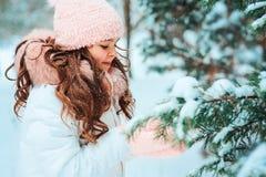 Winterporträt des glücklichen Kindermädchens im weißen Mantel und im Hut und des rosa Handschuhspielens im Freien im Wald des ver stockbild