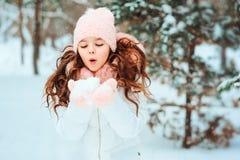 Winterporträt des glücklichen Kindermädchens im weißen Mantel und im Hut und des rosa Handschuhspielens im Freien im Wald des ver lizenzfreie stockfotos