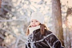 Winterporträt des netten lächelnden Kindermädchens auf dem Weg im sonnigen schneebedeckten Wald Stockbild